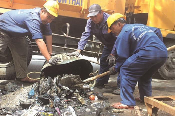 Công nhân Công ty TNHH MTV Thoát nước - Đô thị hàng ngày vớt rác từ lòng cống.